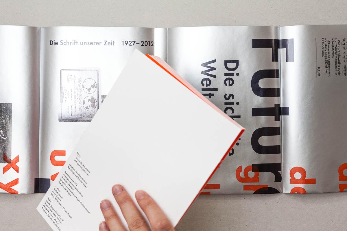 Buch wird aus dem Umschlag genommen Futura – Die sich die Welt eroberte. 10 Fragen und Antworten. © Christian Weber – Büro für Gestaltung und Kommunikation