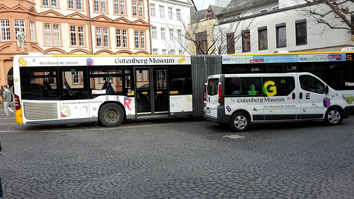 Beklebter Linienbuss und kleiner Bus stehen vor dem Römischen Kaiser – Gutenberg Museum Mainz. Das Museum der Zukunft © Christian Weber – Büro für Gestaltung und Kommunikation